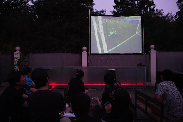 Local football fans watch a World Cup group match projected live on a screen in a Beijing park, on June 13, 2014 (AFP Photo/Greg Baker)