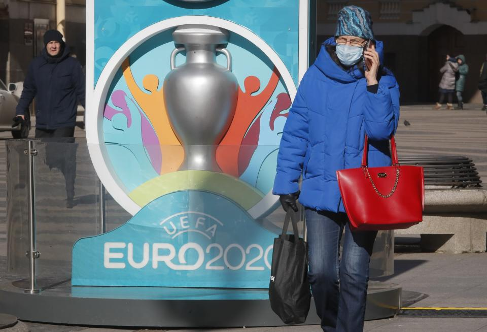 A woman wears a medical mask walks past a sign with Euro 2020 emblem in St.Petersburg where UEFA planned to host four UEFA EURO 2020 matches, including a quarter final, in Russia, Tuesday, March 17, 2020. UEFA today announced the postponement of its flagship national team competition, UEFA EURO 2020, due to be played in June and July this year, avoiding placing any unnecessary pressure on national public services involved in staging matches. For some people the new COVID-19 coronavirus causes only mild or moderate symptoms, but for some it can cause more severe illness. (AP Photo/Dmitri Lovetsky)