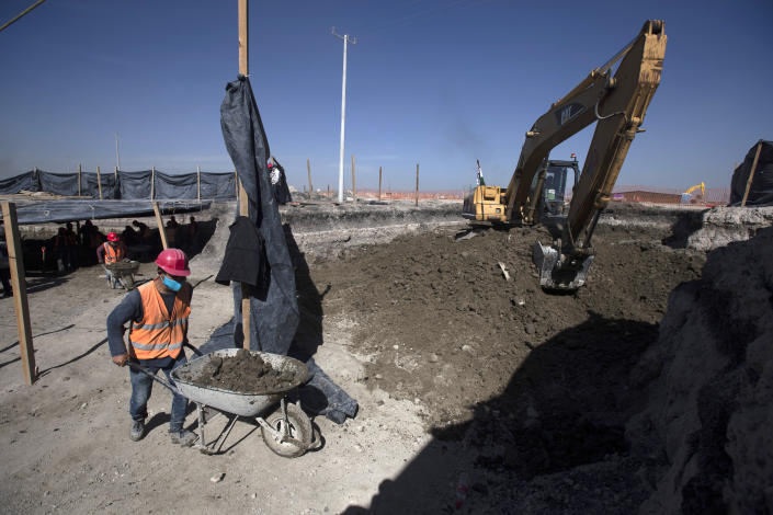 Workers bring out wheelbarrows of dirs as paleontologists work to preserve the skeleton of a mammoth that was discovered at the construction site of Mexico City's new airport in the Santa Lucia military base, Mexico, Thursday, Sept. 3, 2020. The paleontologists are busy digging up and preserving the skeletons of mammoths, camels, horses, and bison as machinery and workers are busy with the construction of the Felipe Angeles International Airport by order of President Andres Manuel Lopez Obrador. (AP Photo/Marco Ugarte)