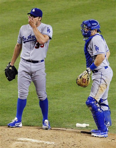 Los Angeles Dodgers' Chris Capuano, left, wipes his face as he gets a visit from catcher Matt Treanor after Capuano gave up a run to the Arizona Diamondbacks during the fourth inning of a baseball game, Monday, May 21, 2012, in Phoenix. (AP Photo/Ross D. Franklin)