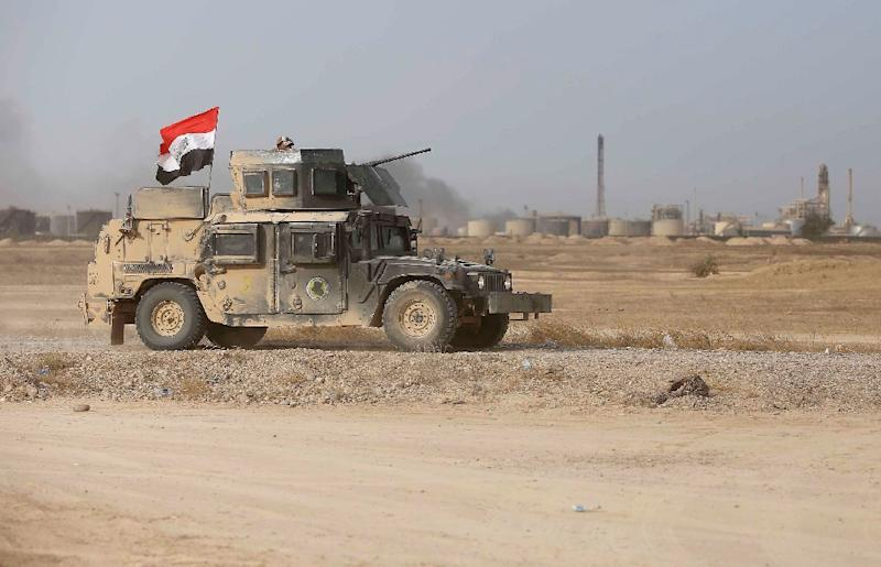 Iraqi Shiite fighters from the Popular Mobilisation units drive their armoured vehicle past Baiji's main refinery on October 15, 2015 (AFP Photo/Mohammed Sawaf)
