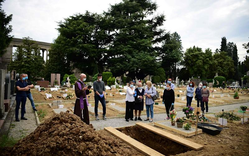 Father Marco Bergamelli (3rdL) prays with relatives of a deceased person during a burial at the Monumental Cemetery of Bergamo, Lombardy - AFP