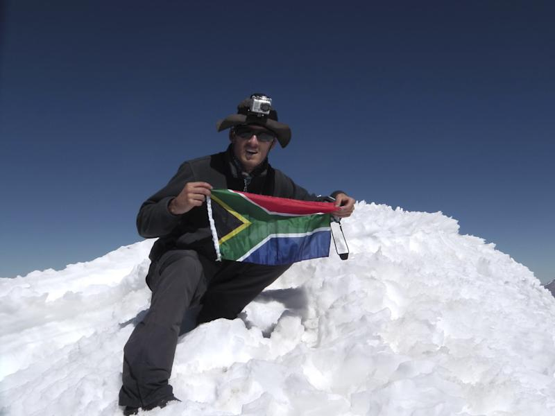 In this undated photo released on Monday Aug. 27, 2012 by the family of South African adventurer David du Plessis, 24, du Plessis holds up the flg of South Africa as he reaches the summit of Mount Mismi located in the Andes mountain range of Peru. David du Plessis, 24, was shot three times and robbed by two young men Saturday, Aug. 25,  while seeking to follow the Amazon River from its origin to its mouth. He is now in stable condition at a Lima hospital. (AP Photo/David du Plessis family)