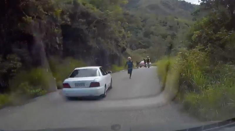 One man can be seen desperately giving chase as the Australian father speeds at reverse back up the steep and windy mountain. Source: Facebook