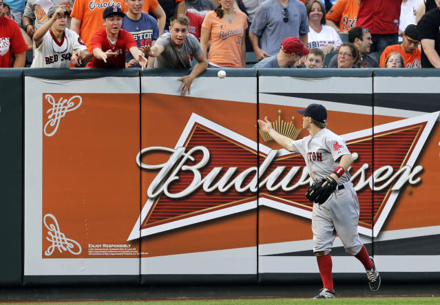 Boston Red Sox left fielder Brock Holt tosses a ball to fans after catching Baltimore Orioles' Chris Davis' fly ball to end the first inning of a baseball game, Monday, June 9, 2014, in Baltimore. (AP Photo/Patrick Semansky)