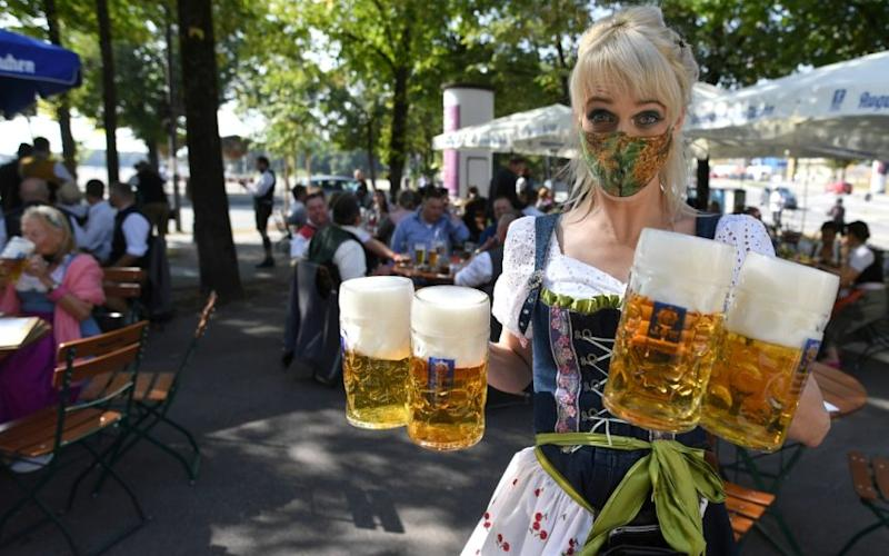 A masked server carries mugs at a beer garden in Munich, Germany - Reuters