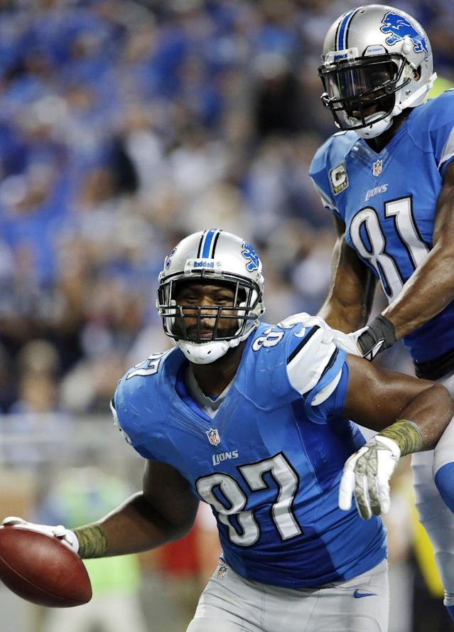 Detroit Lions tight end Brandon Pettigrew (87) is congratulated by teammate Calvin Johnson after his 18-yard touchdown reception during the third quarter of an NFL football game against the Tampa Bay Buccaneers at Ford Field in Detroit, Sunday, Nov. 24, 2013. (AP Photo/Duane Burleson)