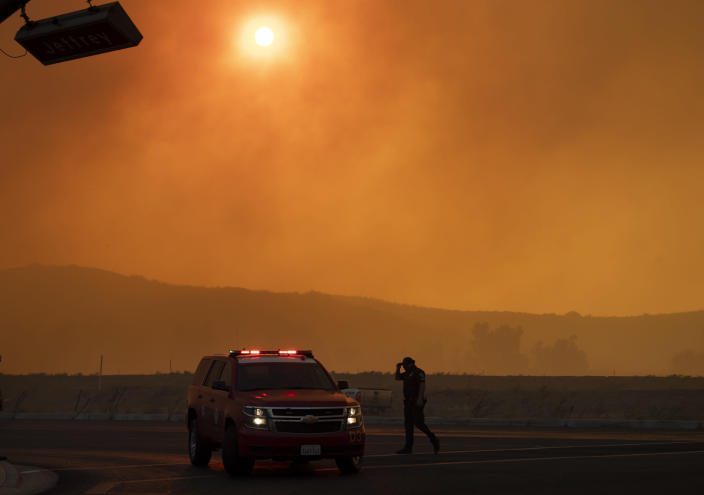 Police and firefighters are out in full force on Jeffrey and Portola in Irvine, Calif., where smoke fills the sky from the wind-driven Silverado wildfire on Monday, Oct. 26, 2020. (Mindy Schauer/The Orange County Register via AP)