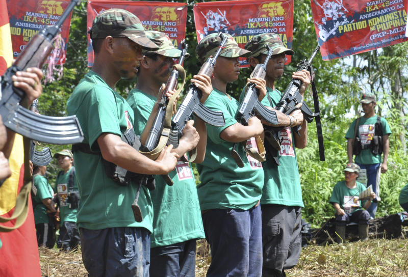 FILE - In this Thursday, Dec. 26, 2013, file photo, Communist New People's Army (NPA) rebels hold weapons in formation in the hinterlands of Davao, Southern Philippines. Justice officials have asked a court to formally designate the Communist Party of the Philippines and its armed wing, the New People's Army, as terrorist groups in a move that could further damage chances of a resumption of stalled peace talks. (AP Photo, File)
