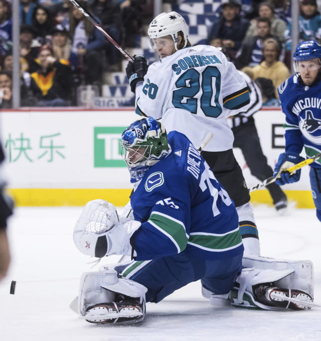 Vancouver Canucks goalie Michael DiPietro (75) makes save as San Jose Sharks' Marcus Sorensen, of Sweden, watches during the first period of an NHL hockey game in Vancouver, British Columbia, on Monday, Feb. 11, 2019. (Darryl Dyck/The Canadian Press via AP)