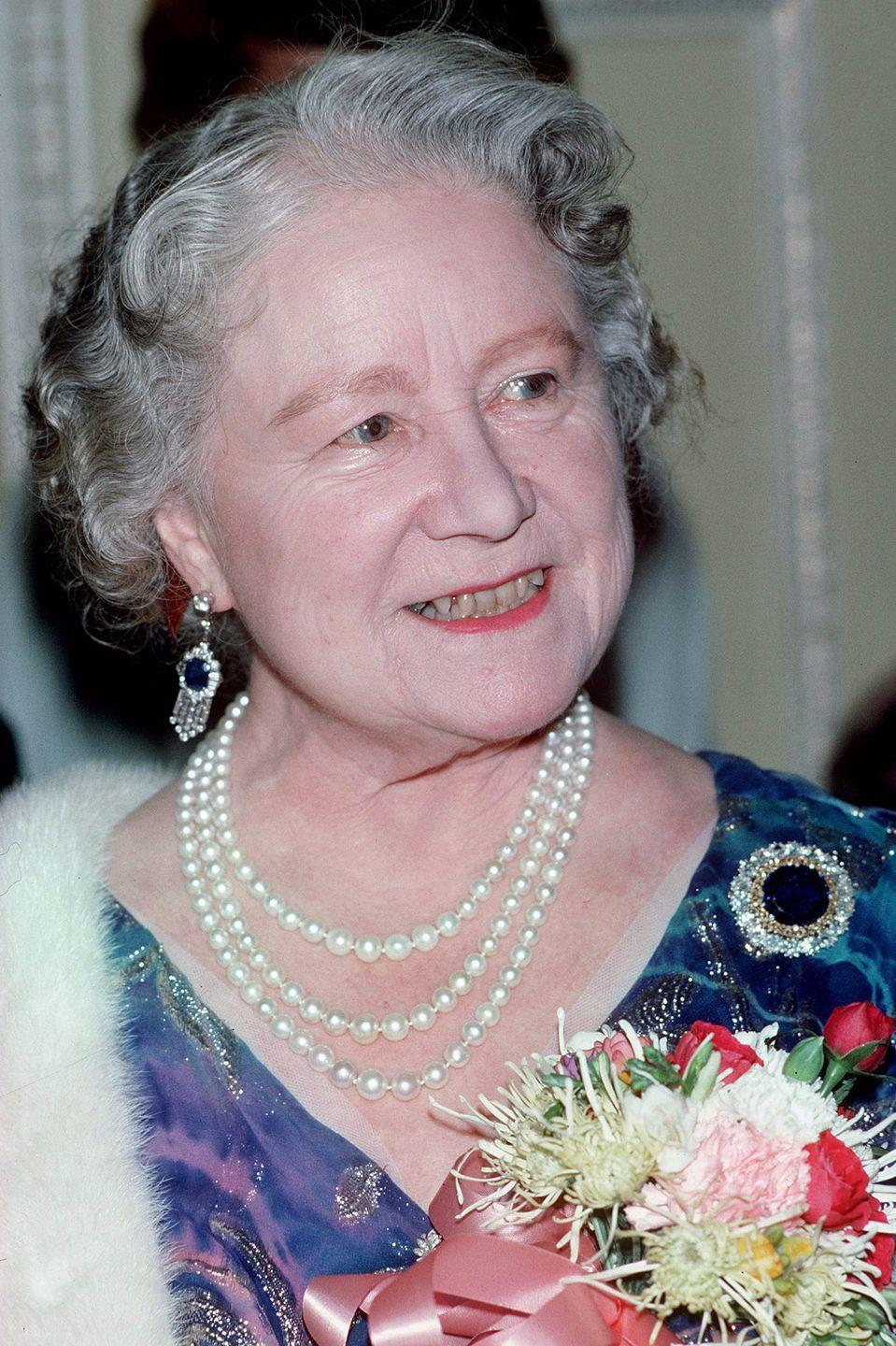 <p>The Queen Mother is pictured here in 1986 wearing her beloved Russian Sapphire Cluster Brooch with a pair of sapphire and diamond fringe earrings.</p>