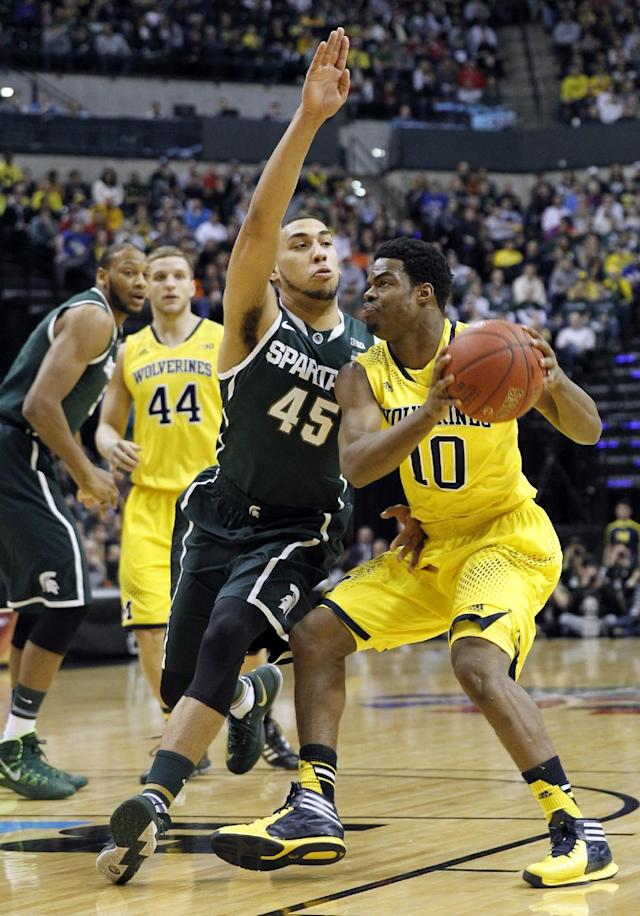 Michigan guard Derrick Walton Jr. (10) drives to the basket against Michigan State guard Denzel Valentine (45) in the first half of an NCAA college basketball game in the championship of the Big Ten Conference tournament on Sunday, March 16, 2014, in Indianapolis. (AP Photo/Kiichiro Sato)
