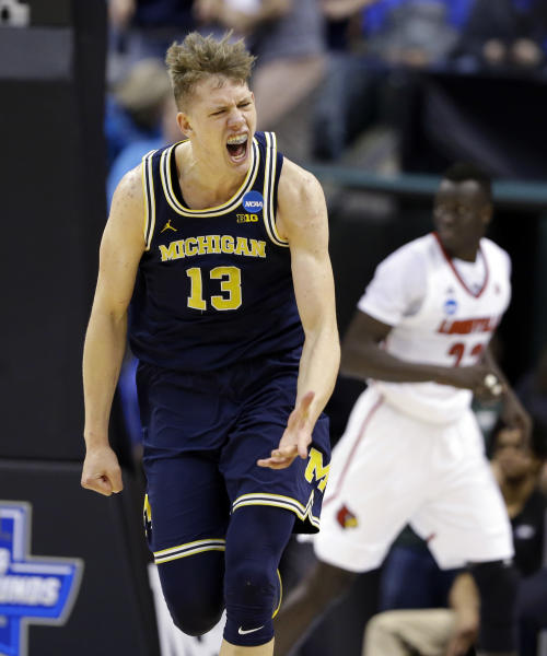 Michigan forward Moritz Wagner (13) celebrates a basket against Louisville during the first half of a second-round game in the men's NCAA college basketball tournament in Indianapolis, Sunday, March 19, 2017. (AP Photo/Michael Conroy)