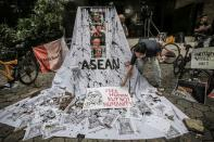 A woman prepares a placard out of crossed out portraits of Myanmar's junta chief Senior General Min Aung Hlaing during protest against the military coup in Myanmar, in Jakarta