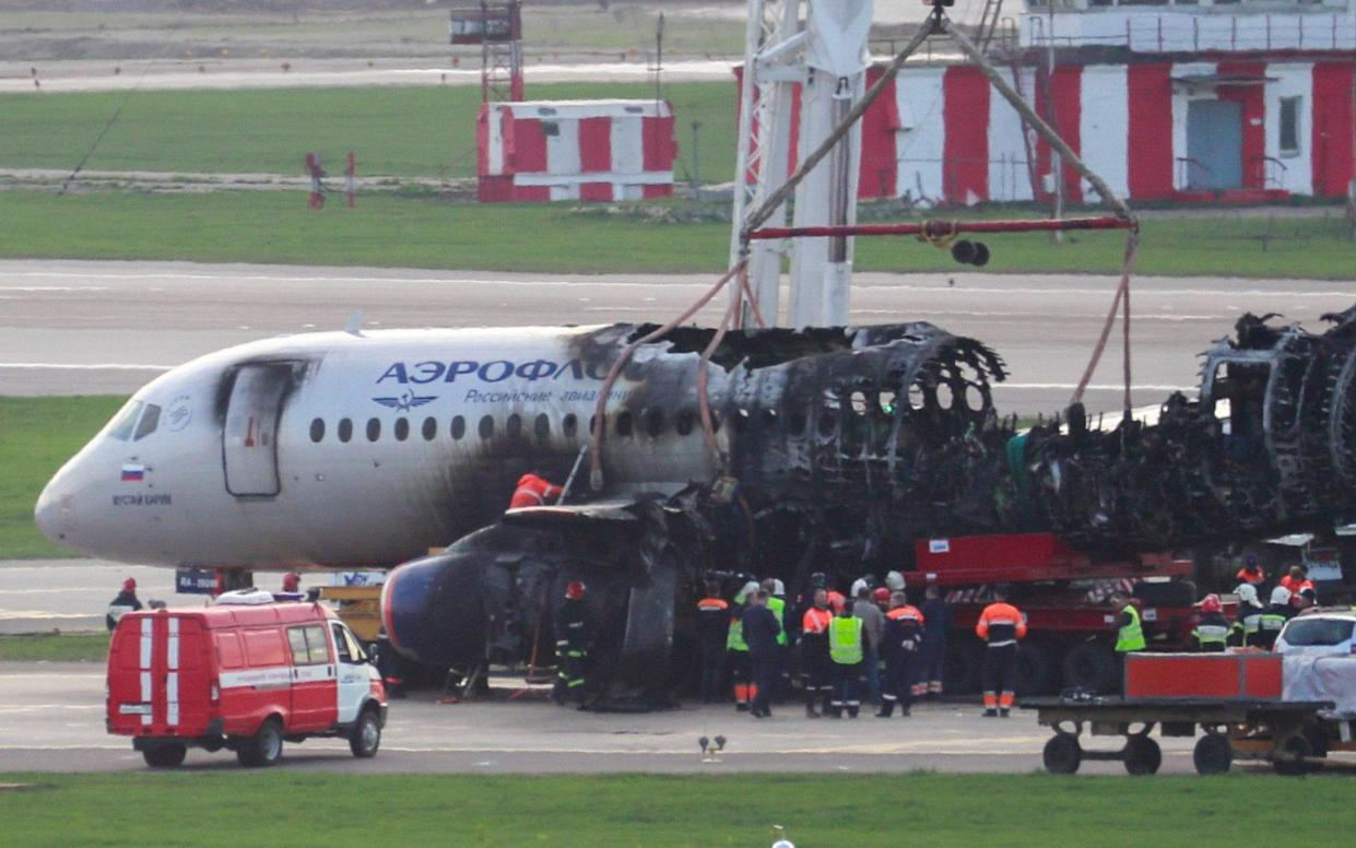 Workers remove the Sukhoi Superjet 100, which caught fire during an emergency landing after a lightning strike, from the runway on Monday - TASS / Barcroft Media