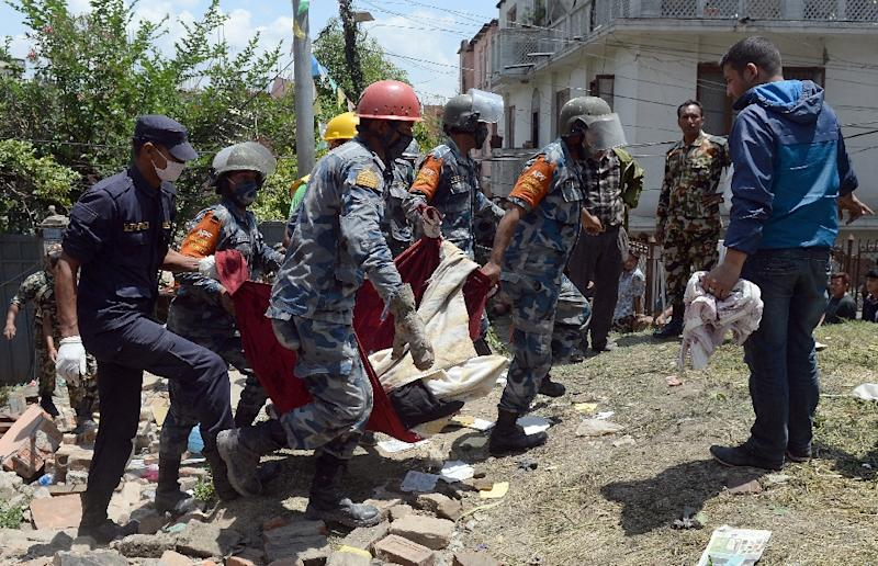 Nepalese police retrieve the body of an earthquake victim during rescue efforts in Kathmandu, on April 27, 2015 (AFP Photo/Prakash Singh)