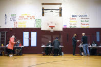 Voters check in to receive ballots at the Domus Kids, inc. polling place on Election Day, Tuesday, Nov. 3, 2020, in Stamford, Conn. (AP Photo/Jessica Hill)