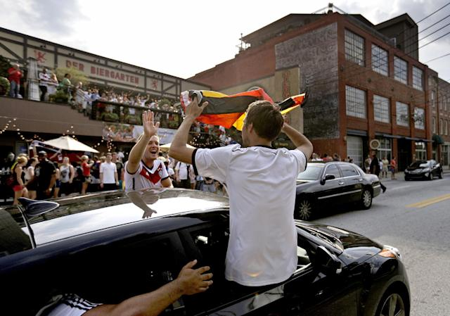 German fans celebrate in the street outside the Der Biergarten restaurant after Germany defeated Argentina in the 2014 World Cup soccer final match, Sunday, July 13, 2014, in Atlanta. (AP Photo/David Goldman)