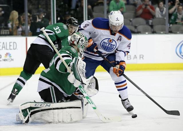 Dallas Stars' Kari Lehtonen (32) of Finland defends the net as Edmonton Oilers left wing Taylor Hall (4) attempts a shot in the second period of an NHL Hockey game, Tuesday, Jan. 14, 2014, in Dallas. The Stars' Alex Goligoski (33) watches on the play. (AP Photo/Tony Gutierrez)