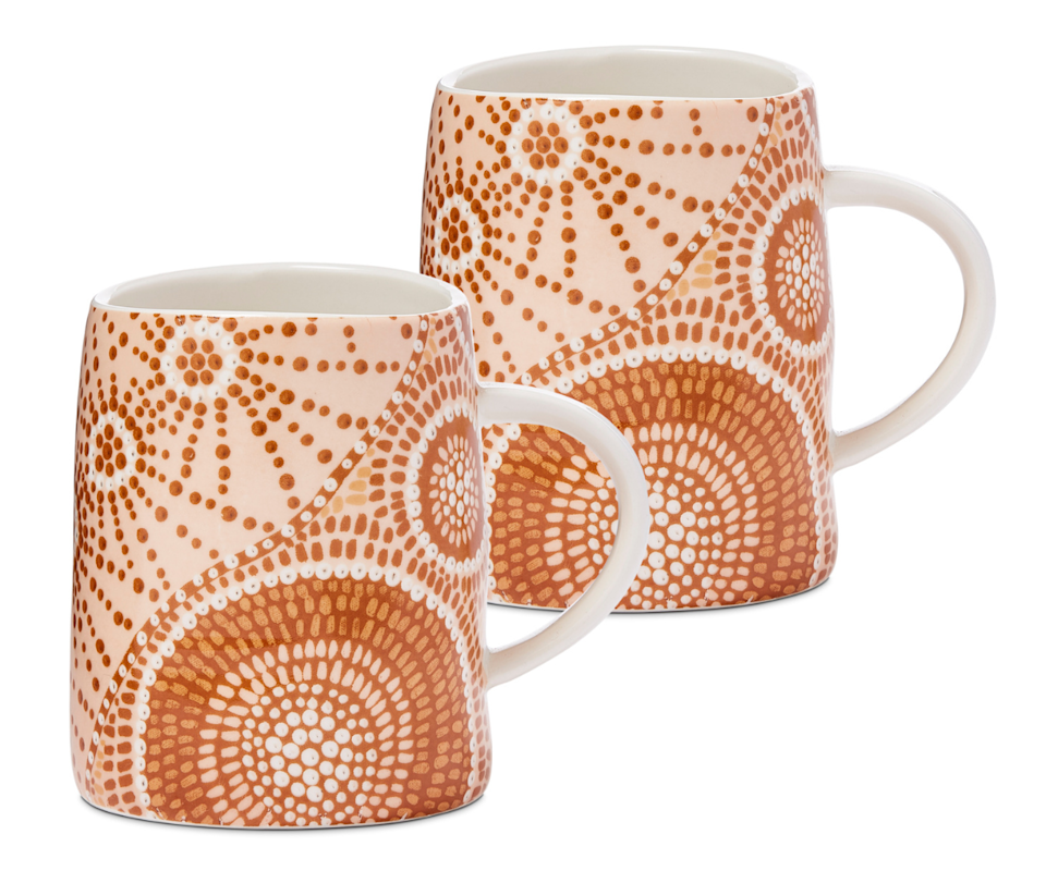 A set of two mugs painted in dark orange indigenous dots.