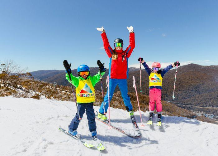 Two children with a ski instructor on top of a snowy mountain at Thredbo
