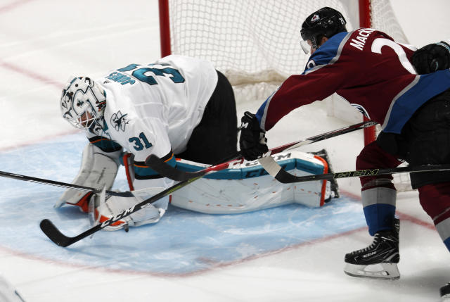 San Jose Sharks goaltender Martin Jones, left, covers the puck after stopping a shot by Colorado Avalanche center Nathan MacKinnon during the third period of Game 4 of an NHL hockey second-round playoff series Thursday, May 2, 2019, in Denver. The Avalanche won 3-0. (AP Photo/David Zalubowski)