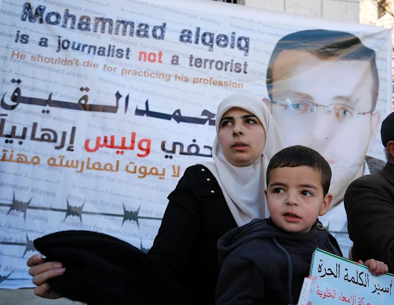 The wife of Palestinian imprisoned journalist Mohammed al-Qiq, Fayha Shalash, flanked by her son Islam, addresses journalists during a press conference on her husband's health situation on January 31, 2016
