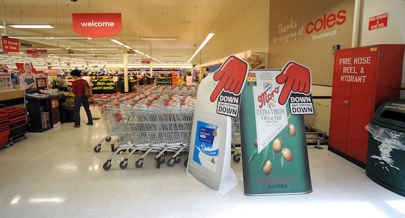 Photo shows the entrance to a Coles store.