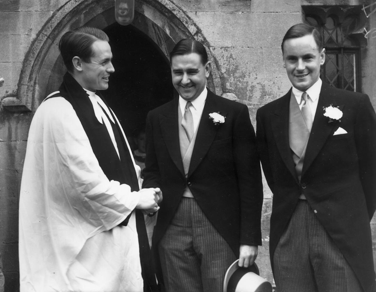 September 1956:  Colin Cowdrey (centre; 1932 - 2000) shakes the hand of the Rev David Sheppard, with his best man Peter May (1929 - 1994) at his side on the occasion of his marriage to Penelope Chiesman at St Nicholas' Church in Chislehurst, Kent; all three men have captained the England cricket team.  (Photo by Topical Press Agency/Getty Images)