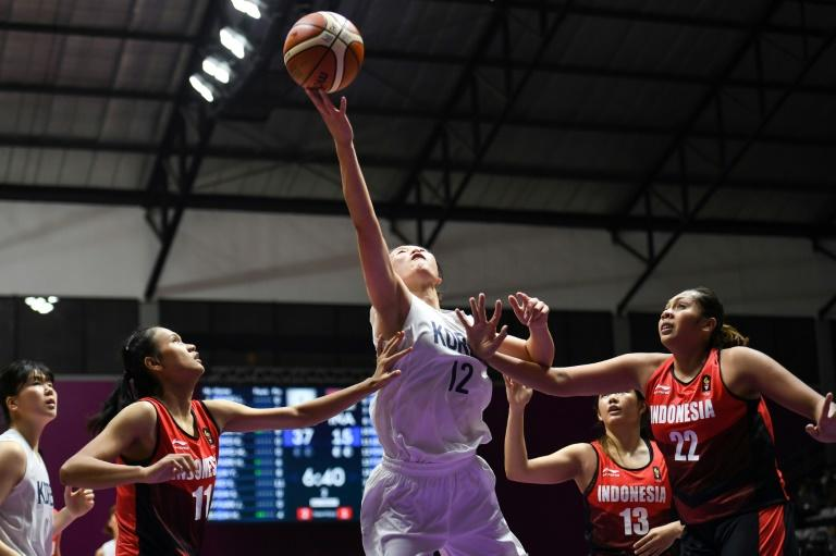 North Korean Ro Suk Yong (C), a member of the Unified Korea basketball team at the Asian Games, top-scored with 22 points, helping her team smash their hosts Indonesia