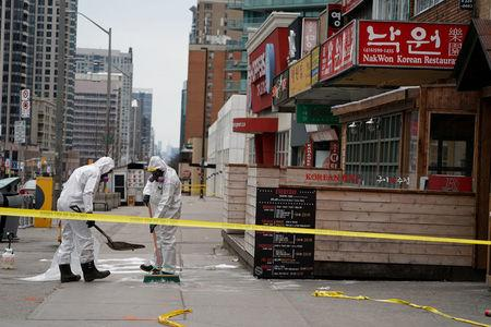FILE PHOTO: Workers clean up blood stains on Yonge Street following a van that attacked multiple people in Toronto