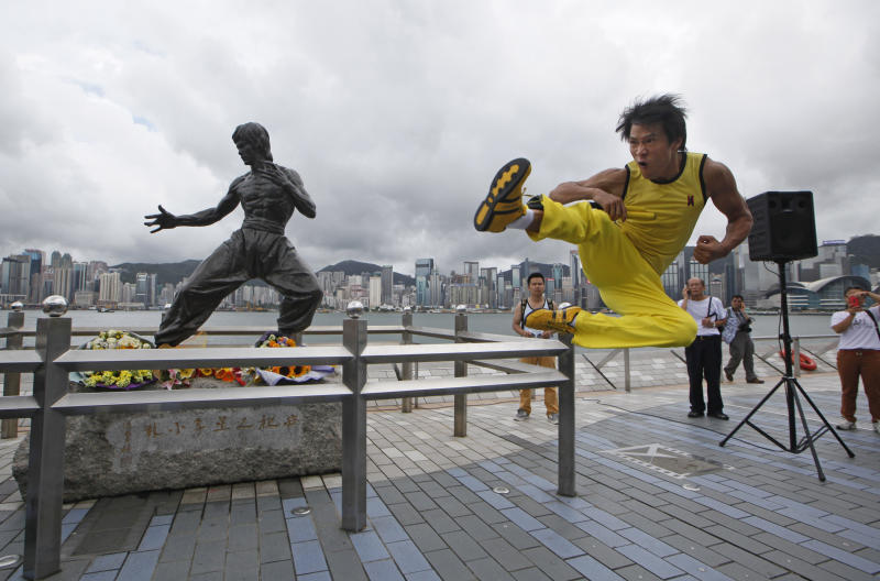 """Chinese actor Mei Zhiyong dressing as the late Hong Kong Kung Fu star Bruce Lee performs in front of the bronze statue in Hong Kong Saturday, July 20, 2013 to commemorate the 40th anniversary of the death of Lee. The late superstar Bruce Lee is best-known for the kung fu skills he displayed in his movies, but his daughter hopes that more people take the effort to understand his teachings and life philosophy. Marking his death 40 years ago on July 20, the Hong Kong government has teamed up with the Bruce Lee Foundation to put together an exhibition to showcase the late star's life, from his famous yellow tracksuit he wore in the movie """"Game of Death,"""" to his writings and drawings. (AP Photo/Kin Cheung)"""