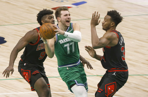 Dallas Mavericks guard Luka Doncic (77) drives inside as Chicago Bulls forward Patrick Williams (9) and center Wendell Carter Jr. (34) defend during the second half of an NBA basketball game, Sunday, Jan. 17, 2021, in Dallas. (AP Photo/Ron Jenkins)