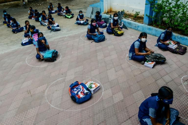 Students in Chennai keep their distance while waiting to collect course materials before heading home to begin online lessons