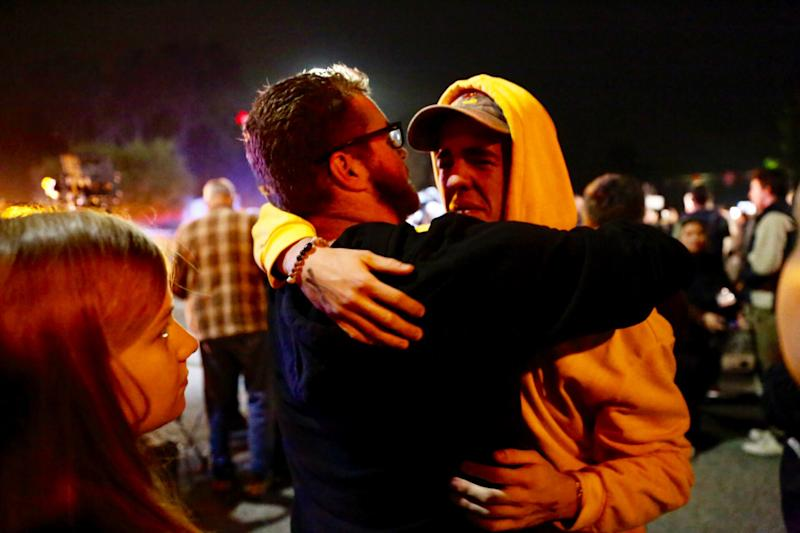 """Holden Harrah, 21, (right), who witnessed the shooting at Borderline Bar &amp; Grill late Wednesday, hugs family and friends.<a href=""""https://www.huffingtonpost.com/entry/photos-show-scene-outside-thousand-oaks-bar-after-mass-shooting-leaves-12-dead_us_5be44733e4b0e8438894d380#5be44559e4b0e8438894ca2a"""" data-ylk=""""subsec:entry-image;itc:0"""" data-rapid-parsed=""""slk"""" data-rapid_p=""""1"""" data-v9y=""""1""""></a> (Photo: Al Seib via Getty Images)"""