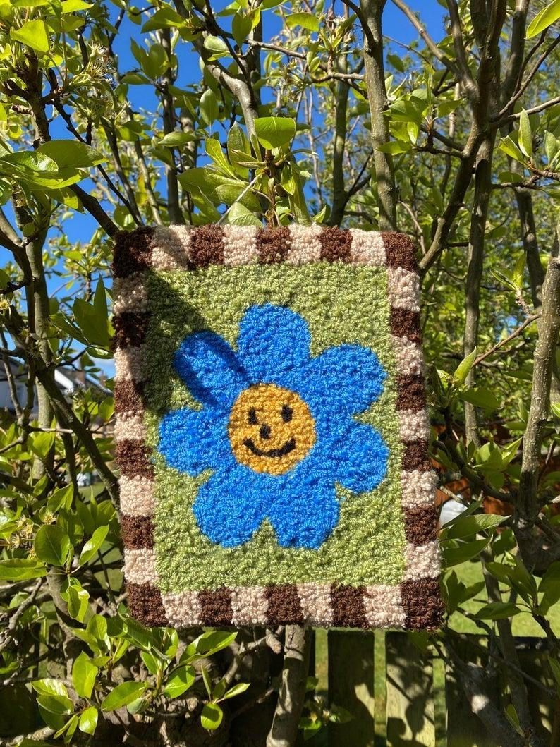 """Whether hanging from your wall or placed on your floor, this smiley friend is a playful addition to your space.<br><br><strong>Moonwavey</strong> Smiley Flower Tufted Wall Hanging, $, available at <a href=""""https://www.etsy.com/uk/listing/1017826525/smiley-flower-tufted-wall-hanging?"""" rel=""""nofollow noopener"""" target=""""_blank"""" data-ylk=""""slk:Etsy"""" class=""""link rapid-noclick-resp"""">Etsy</a>"""