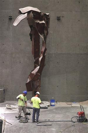 """Construction workers work under steel facade segments, also known as """"Impact Steel"""", that were torn apart when hijacked United Flight 175 tore into the South Tower of the World Trade Center on September 11, 2001, as it hangs inside a center passage area of The National September 11 Memorial and Museum, which is under construction, at the World Trade Center site in New York in this September 6, 2013 file photo. REUTERS/Brendan McDermid/Files"""