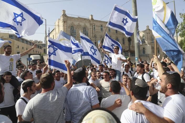 """FILE - In this May 10, 2021, file photo, Israelis wave national flags during a Jerusalem Day march, in Jerusalem. At the last minute, the Israeli government ordered marchers to change their route, but by then it was too late. Hamas, saying it was protecting Jerusalem, launched a barrage of long-range rockets at the city, crossing an Israeli """"red line"""" and sparking the war. (AP Photo/Ariel Schalit, File)"""