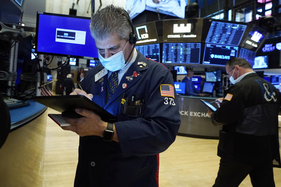 Trader John Panin, left, works on the floor of the New York Stock Exchange, Tuesday, Aug. 10, 2021. Stocks rose in morning trading on Wall Street Tuesday as energy companies and banks clawed back some of the ground they lost a day earlier. (AP Photo/Richard Drew)
