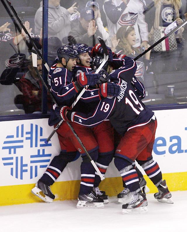 Columbus teammates mob R.J. Umberger after he scored the game-winning goal against Vancouver during the third period of an NHL hockey game Sunday, Oct. 20, 2013, in Columbus, Ohio. (AP Photo/ Mike Munden)