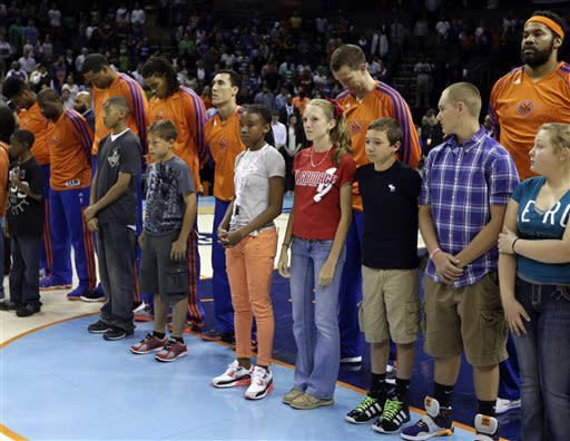 New York Knicks players and children bow their heads in a moment of silence for the victims of the explosions at the Boston Marathon before an NBA basketball game against the Charlotte Bobcats in Charlotte, N.C., Monday, April 15, 2013. (AP Photo/Chuck Burton)