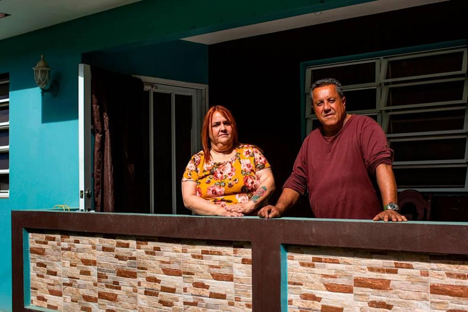 Elba Santos and David González, parents of Angie González, stand outside their house in Barranquitas, Puerto Rico, on March 21, 2021.