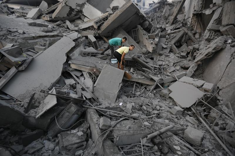 Palestinian residents inspect the remains of Al-Basha, a building that was destroyed by an Israeli air strike in Gaza City on August 26, 2014