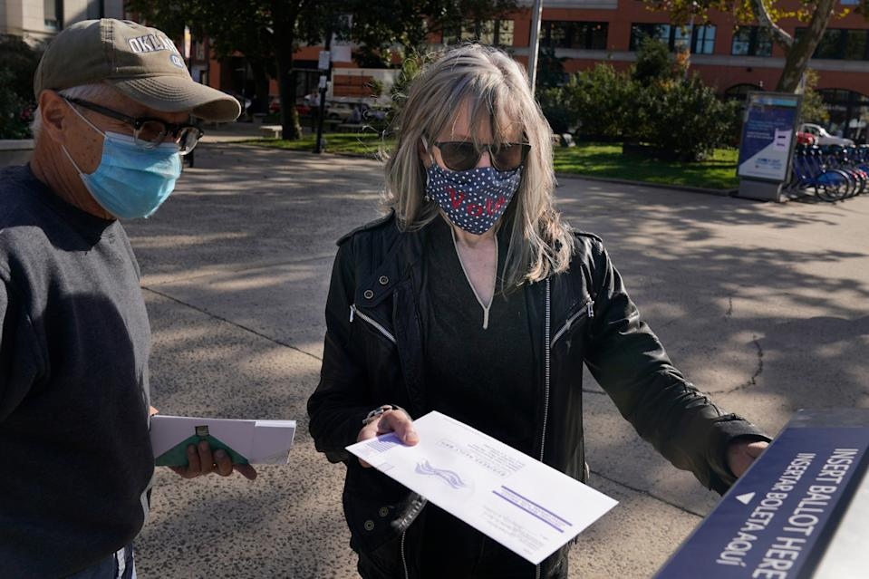 """Caroline Burton, wearing a mask that says """"Vote"""", and her husband Thomas English drop their ballots in an election drop box in Jersey City, N.J., on Thursday, Oct. 15, 2020."""