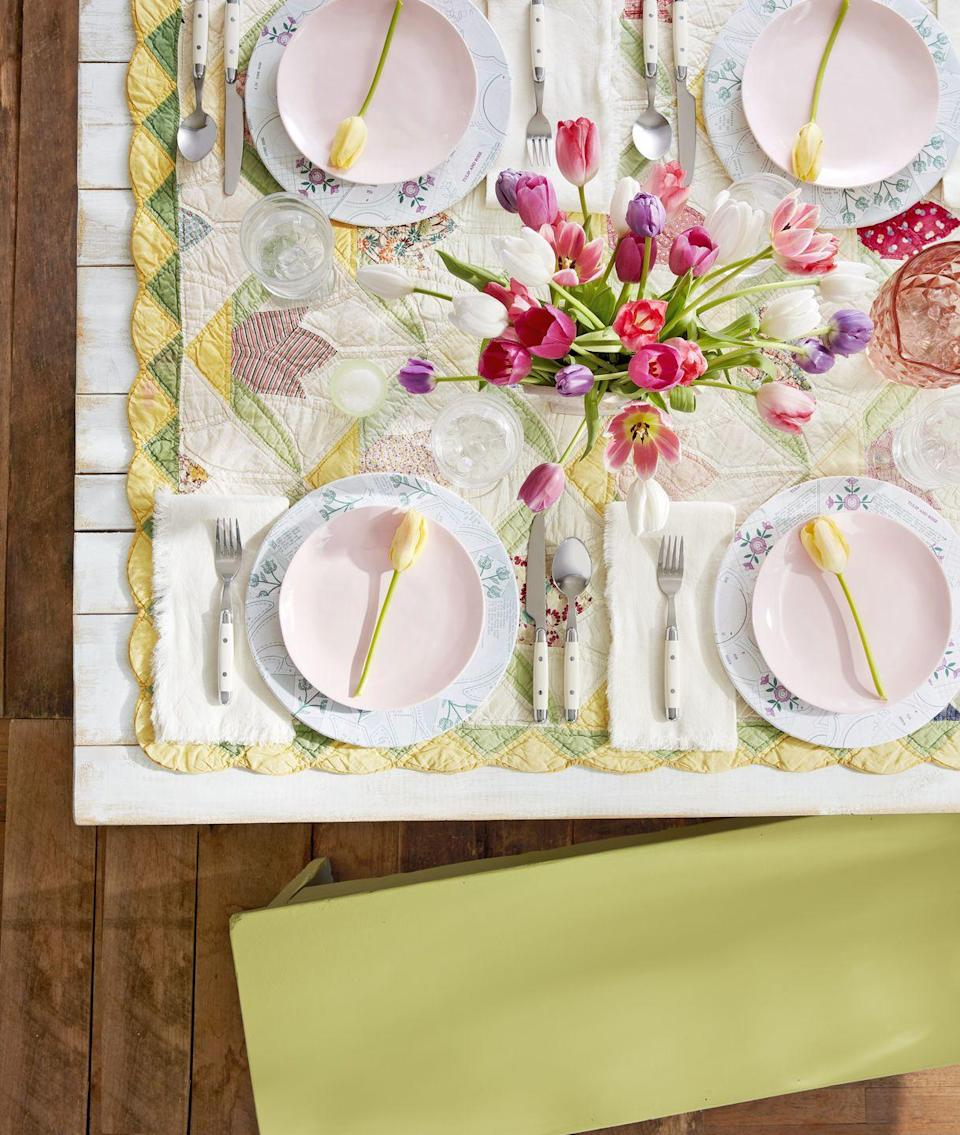 """<p>Put grandma's (or your own!) springtime quilt to good use-smack dab on the center of the table. Match the rest of your settings and centerpieces around this sentimental tablescape base.</p><p><a rel=""""nofollow noopener"""" href=""""https://www.amazon.com/Vintage-Disposable-Round-Plastic-Plates/dp/B07371XH7Y/r"""" target=""""_blank"""" data-ylk=""""slk:SHOP SPRING PLATES"""" class=""""link rapid-noclick-resp"""">SHOP SPRING PLATES</a></p>"""