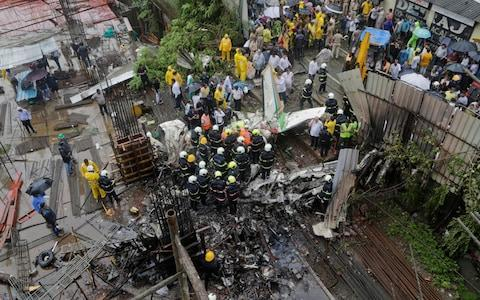 <span>Rescuers stand amid the wreckage of a private chartered plane that crashed in Ghatkopar area, Mumbai</span> <span>Credit: Rajanish Kakade/AP </span>