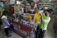 People wearing face masks and face shields to prevent the spread of the coronavirus buy at a grocery in Quezon city, Philippines as they prepare for a stricter lockdown on Sunday March 28, 2021. The government will start stricter lockdown measures next week as the country struggles to control an alarming surge in COVID-19 cases. (AP Photo/Aaron Favila)
