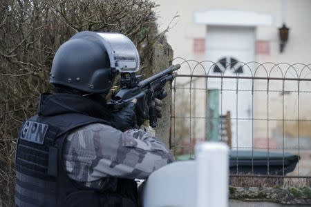 A member of the French GIPN intervention police forces secures a neighbourhood in Corcy, northeast of Paris January 8, 2015. REUTERS/Christian Hartmann