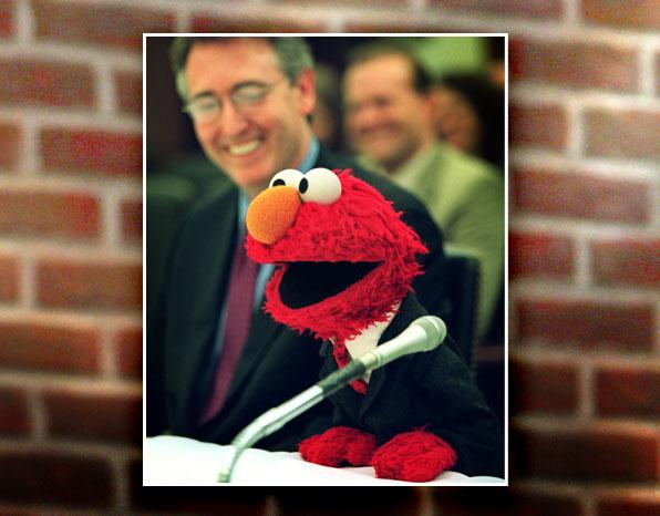"""His street is in New York, but Elmo has traveled around the world. His 2002 visit to Capitol Hill was a first for a couple reasons: He was the only non-human ever to testify before Congress, and he wore clothes (a suit, in fact) for the occasion. Elmo <a href=""""http://articles.cnn.com/2002-04-23/politics/elmo.hill_1_elmo-instruments-congressional-committee?_s=PM:ALLPOLITICS"""" rel=""""nofollow"""">appeared before the Education Appropriations Subcommittee</a> to argue for funding for music research and instruments. """"Though I wasn't really nervous, I was glad to be under the table — this was Congress, after all,"""" writes Clash in his autobiography."""