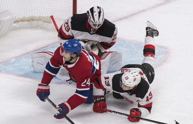 Montreal Canadiens' Phillip Danault (24) collides with New Jersey Devils goaltender Mackenzie Blackwood and Nico Hischier (13) during first-period NHL hockey game action in Montreal, Thursday, Nov. 28, 2019. (Graham Hughes/The Canadian Press via AP)
